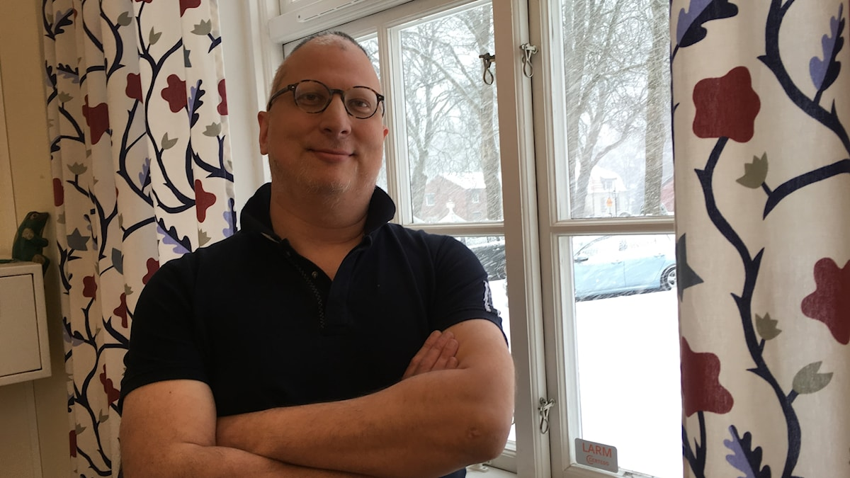 En man står framför ett fönster med blommiga gardiner