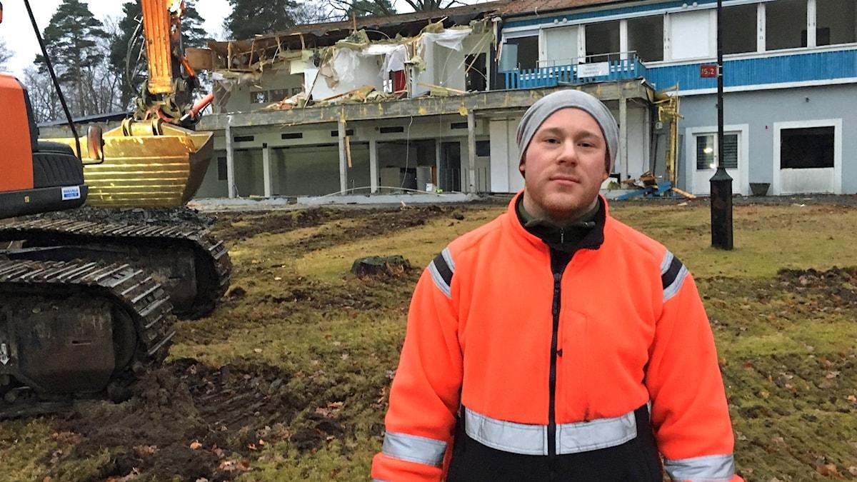 Till vänster en rivningsmaskin med grävskopa och i bakgrunden syns husbyggnader som börjat rivas. I förgrunden står Timmy Carlqvist som arbetar med rivningen.