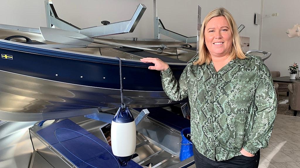 Jessica Linder, marknadschef på Linder Aluminiumbåtar i Tingsryd framför en båt.