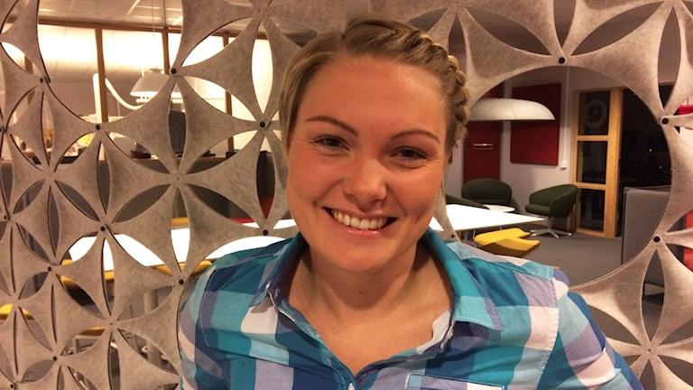 Sofia Olofsson står och ler stort med tänderna.