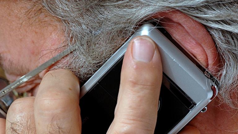 Äldre man i 60-årsåldern pratar i sin mobiltelefon