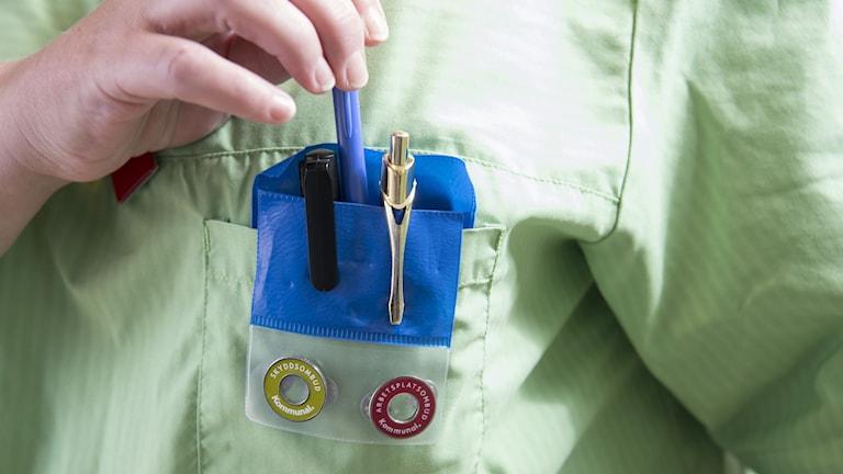 en undersköterska sätter ner pennor i sin bröstficka.