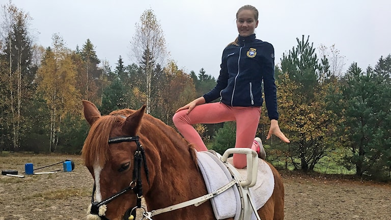 Kajsa Rimskog står på en hästrygg