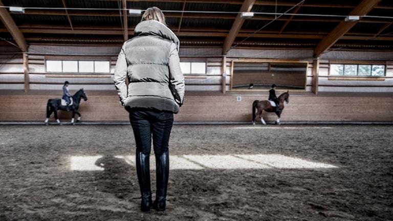 En ridmanege med två ridande tjejer och en som står och ser på när de rider. Anonyma personer som inte har med artikeln att göra.