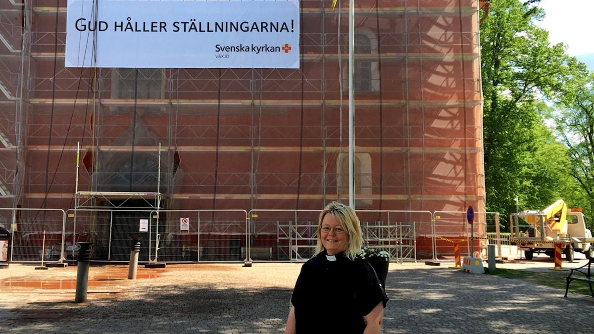 Pastoralchef Åsa Ingvert utanför Domkyrkan i Växjö. På fasaden hänger banderollen Gud håller ställningarna.