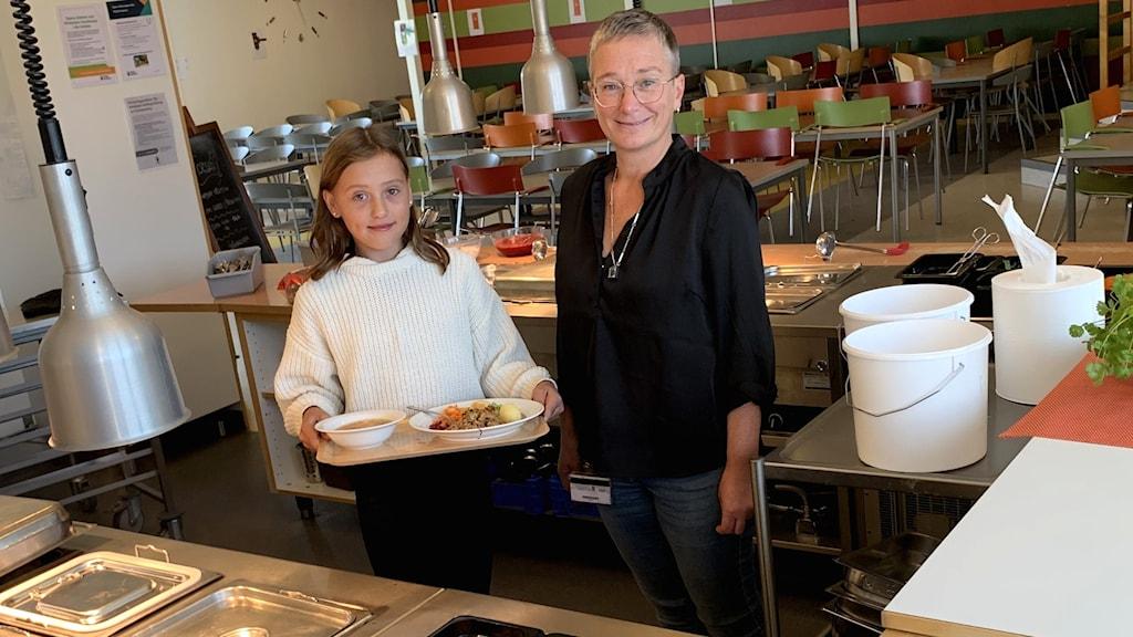 En flicka tillsammans med verksamhetschefen för måltidsenheten.