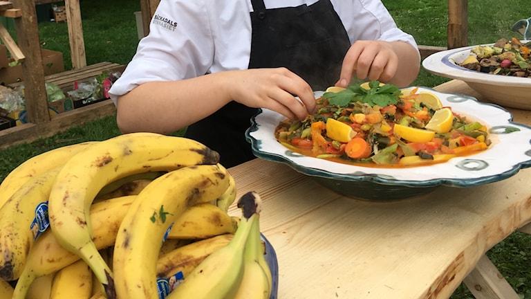 En skål med banan och händer som plockar med mat