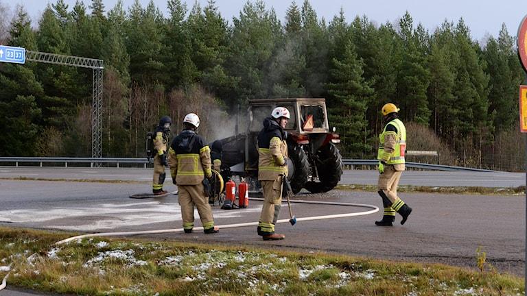 Räddningstjänsten på plats vid den brinnande traktorn.