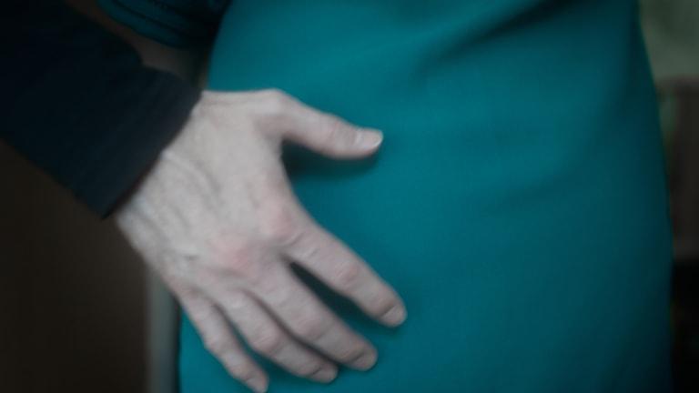 En man lägger handen på en kvinnas höft