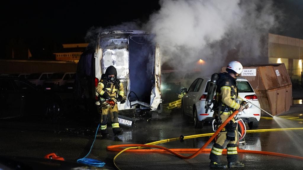 Brandmän med vattenslangar. Det ryker kraftigt från en utbränd skåpbil.