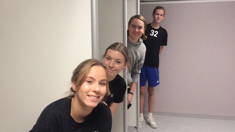 Stina Gustavson, Smilla Fredriksson, Sebastian Christiansen och Samuel Backgård står påklädda i varsitt duschbås i omklädningsrummet och tittar in i kameran och ler.