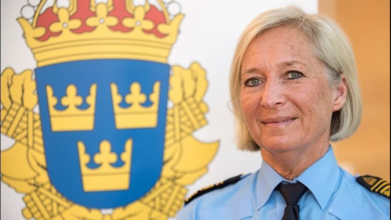 Polischef region syd, Carina Persson. Porträttbild framför en polissymbol.