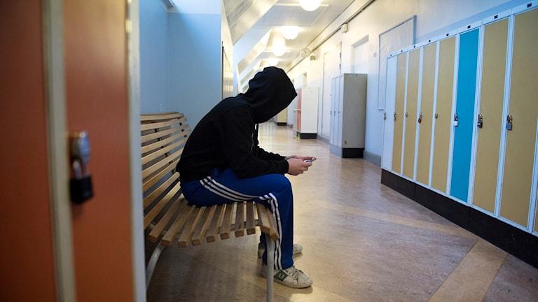 En elev ensam i en skolkorridor