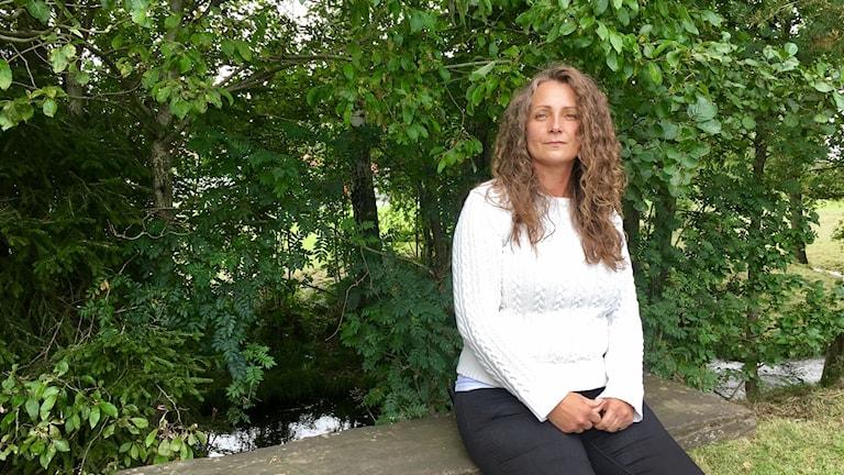 Stina Axbom, sekreterare i föreningen Spes sitter på en träbänk i ett skogsparti.