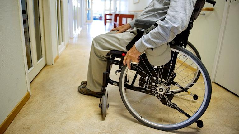 Pensionär i rullstol i en öde korridor. Foto: Jessica Gow/Scanpix.