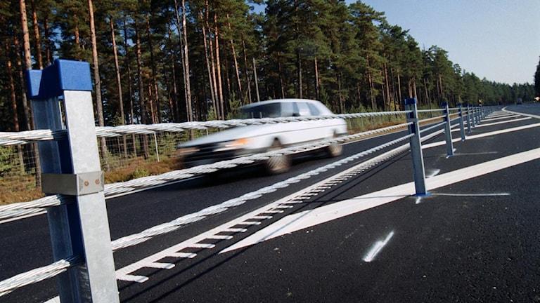 Väg med mitträcke och en bill som kör förbi. Foto: Fredrik Persson/Scanpix.