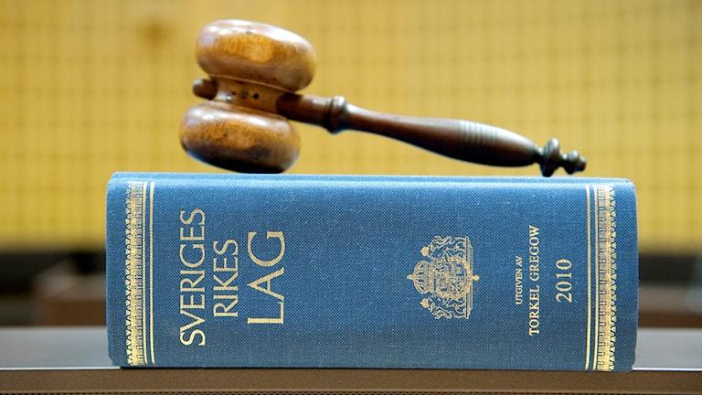 Lagbok och klubba i rättssal.