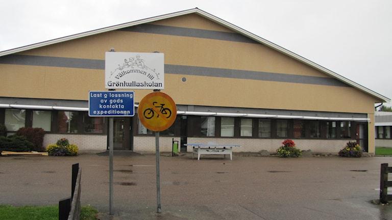 Exteriörbild på Grönkullaskolans byggnad i Alvesta med skylt framför med skolans namn på.