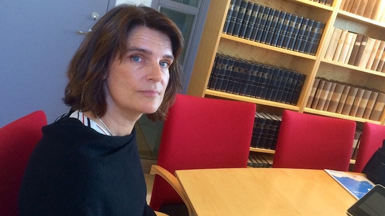 Kammaråklagare Anna-Karin von Schoultz framför en bokhylla.