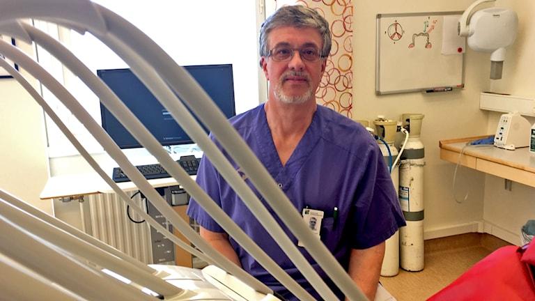 Jan Berdén tandläkare sitter i sitt mottagningsrum med verktyg i förgrunden.