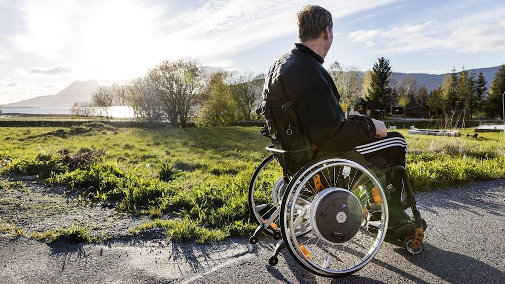 En man sitter i en rullstol.