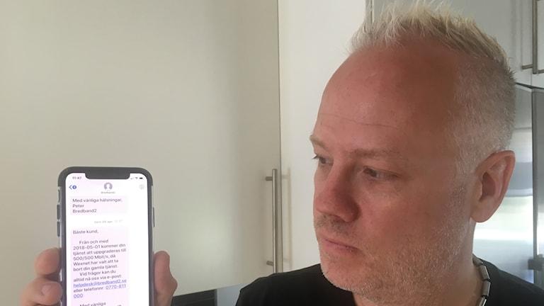 Tommy Arvidsson tittar in i sin telefon där han fått sms av Bredband 2