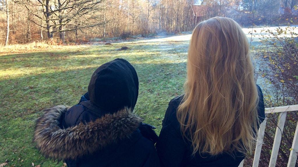 Johanna och Alexandra står på en trappa och tittar ner mot en sjö.