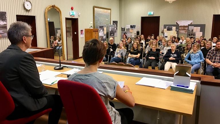 Sjundeklassarna sitter på stolar och lyssnar på kommunfullmäktige