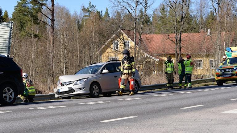 En bil har kört in i bakdelen på en annan bil. Räddningspersonal på platsen.