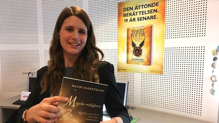 Malin Alkestrand med en bok i handen