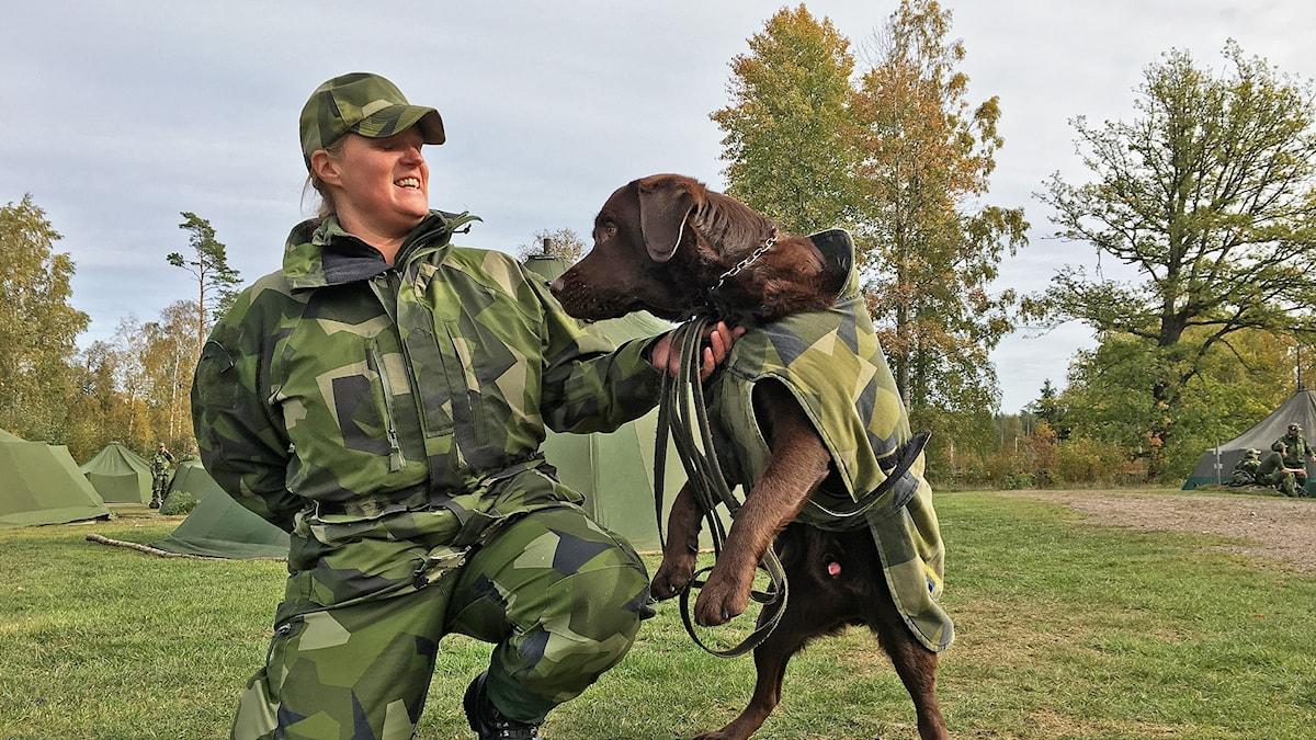 Linda Mandelholm tillsammans med sin hund. De har militärkläder på sig.