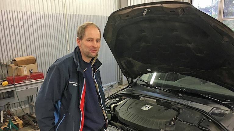 Andreas Petersson står och hänger på motorhuven.