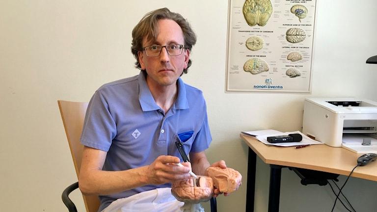 Neurologen Fredrik Schön visar en hjärna
