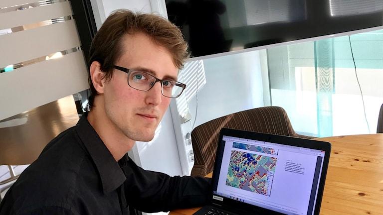 Max van Meeningen, samordnare för klimatanpassning på länsstyrelsen framför en dator med en karta.