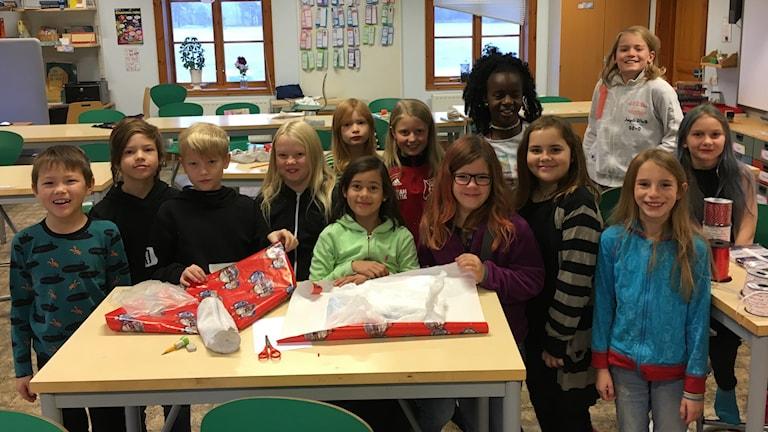 13 barn poserar i sitt klassrum bakom ett bord med julklappar