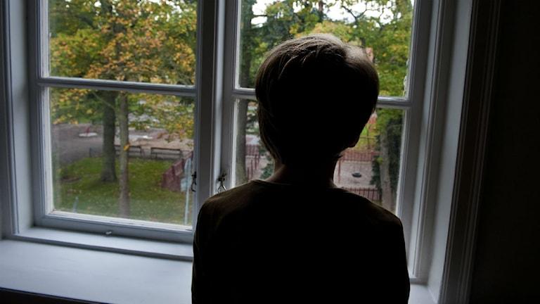 Ett barn i siluett framför fönster. Foto: Scanpix.