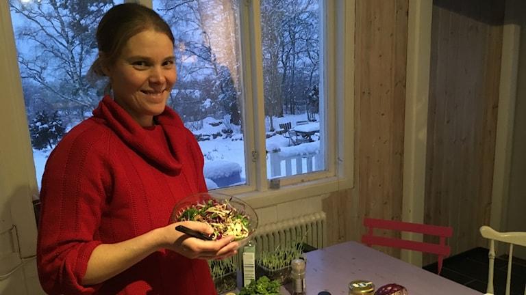 En kvinna står i ett kök vid ett bord och håller upp en skåk med kålsallad