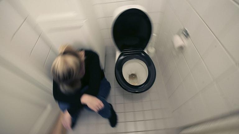 Vinterkräksjukan gör sig påmind i år igen. En kvinna kvinna som mår illa sitter på golvet bredvid en toalettstol. Foto: Fredrik Sandberg/Scanpix