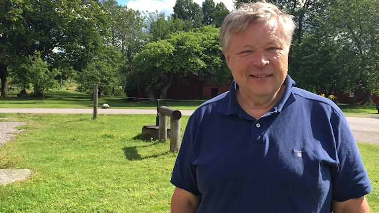 Åke Carlsson står utomhus vid en gräsmassa och har solen i ansiktet.