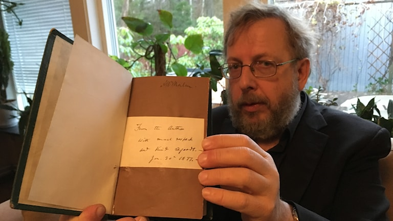 Torbjörn Lindell håller upp en bok där man ser en lapp  med text på en boksida
