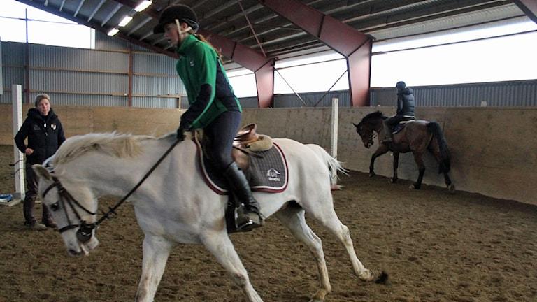 Annie Svensson i Lammhults Ridklubb värmer upp på sin häst framför ridläraren Åsa Svensson. Foto: Anna Tigerström/Sveriges Radio