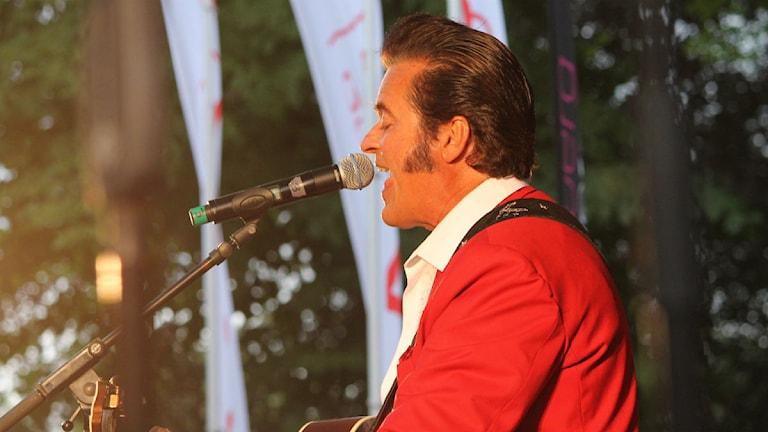 Peter Jesewski med röd kavaj sjunger på scen.