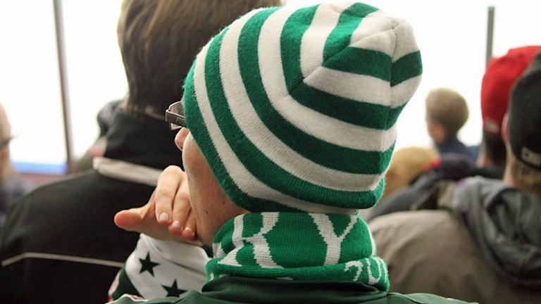 Supporter med grönvit mössa och halsduk.