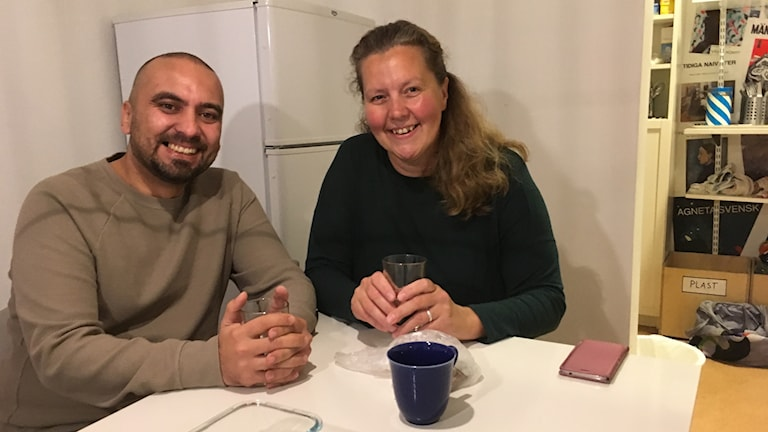 En man och en kvinna sitter vid ett bord och har händerna runt glas med kaffe