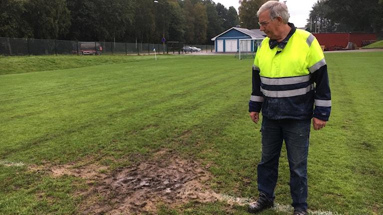 Planskötaren Kurt Arvén inspekterar en av Älmhults IF:s vattensjuka planer.