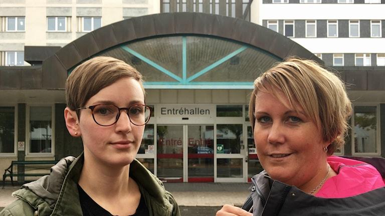 Sjuköterskorna Emelie Wilson och Ellinor Torstensson står utanför sjukhuset i Växjös entré.
