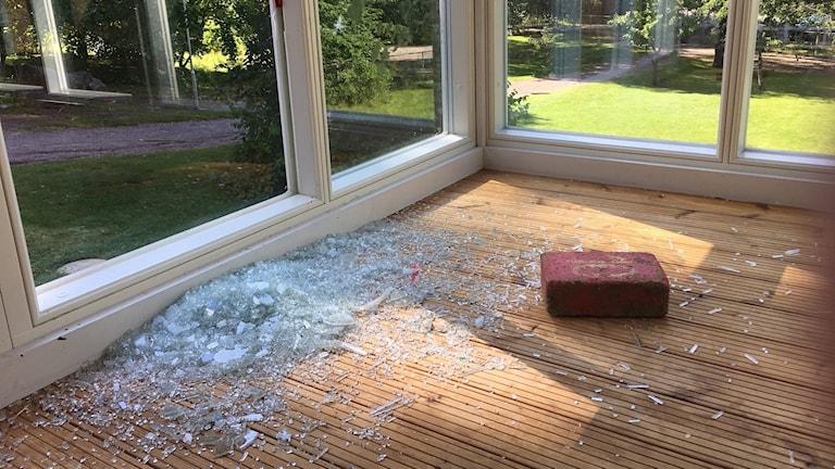 Tegelsten ligger bredvid en krossad fönsterruta.