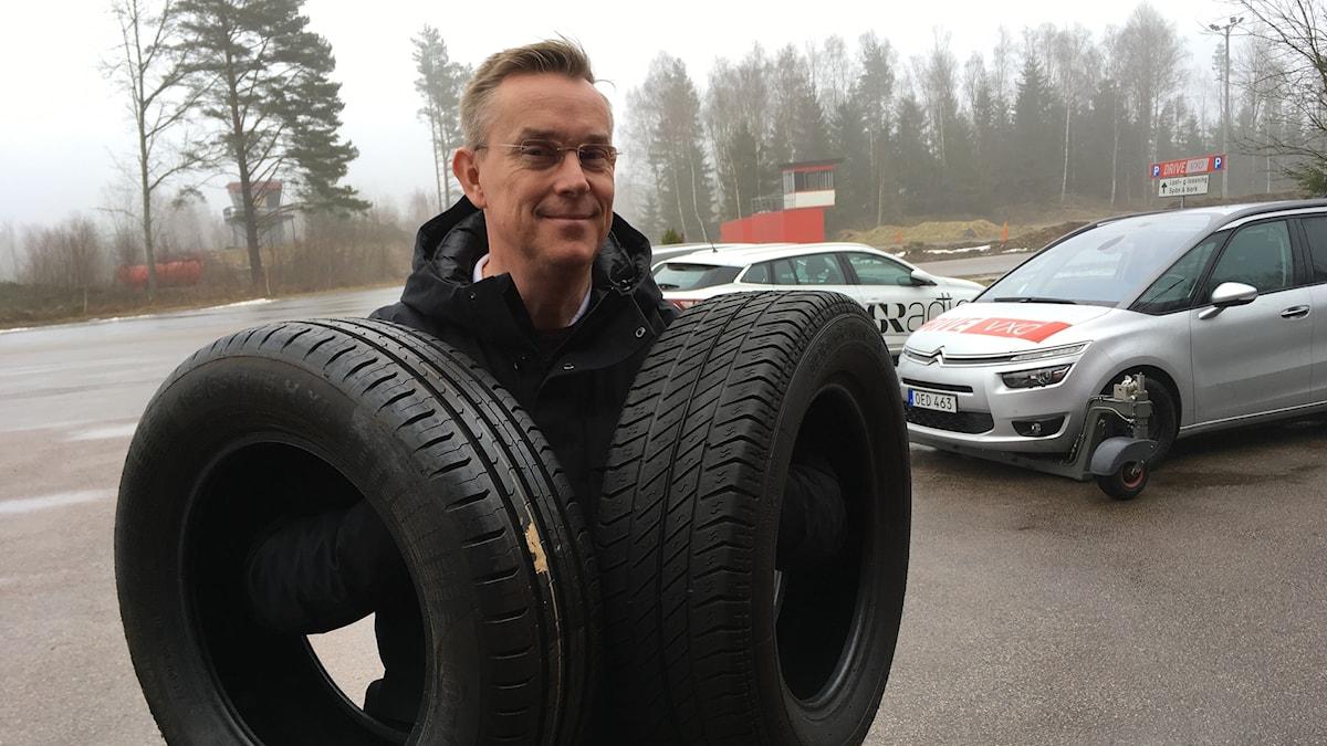 En man står på en parkering och håller upp två bildäck