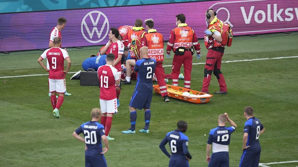 Fotbollsspelare på en fotbollsplan, en spelare ligger skadad med ett hjärtstopp.