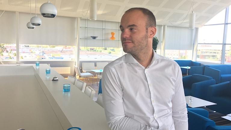 I bild Vismas vd, iklädd vit skjorta. Han lutar sig mot företagets bardisk på högsta våningen. Rummet är vitt och rent med blåa fotöljer.